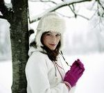 Young woman standing in snow, leaning against tree, portrait